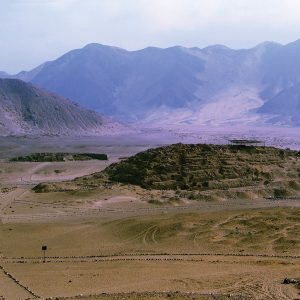 "A view across Caral, one of the earliest urban centres in the world and a key study site for research on prehistoric population history, such as reported in this theme issue. This site, 200km north of Lima in Peru, was inhabited roughly between the 29th and 19th centuries BC by the Norte Chico civilization. The mound seen in the centre is the ""Edificio Piramidal la Cantera"" (the Quarry Pyramidal Building) and the building in the left background is the ""Edificio del Altar Circular"" or Building of the Circular Altar. Image credit: Daniel Sandweiss."